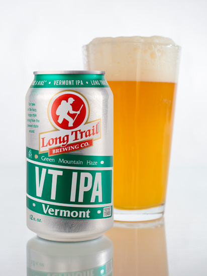 Single VT IPA 12oz can in front of a glass of VT IPA beer