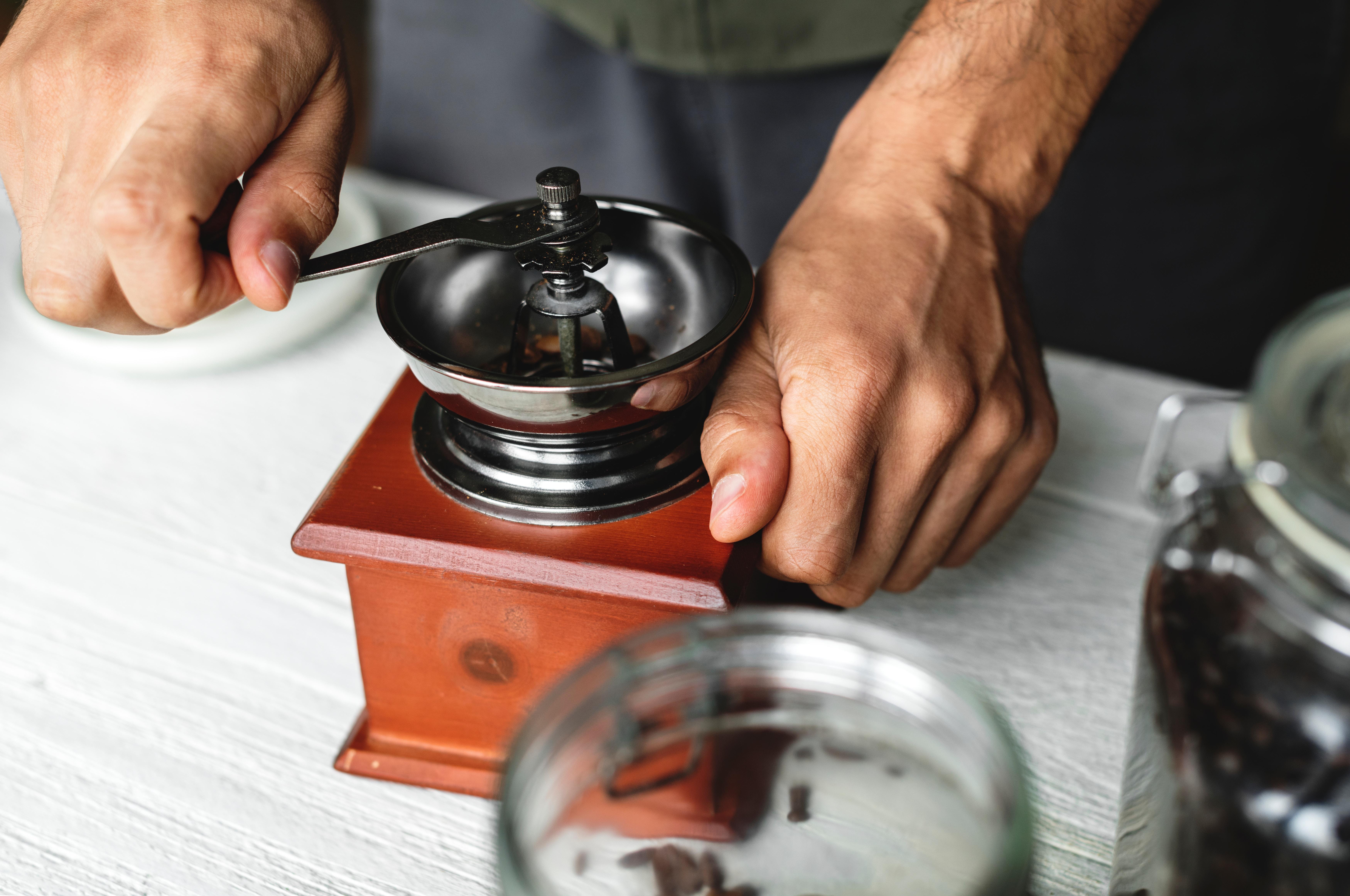 Mielenie ziaren kawy w ręcznym młynku żarnowym