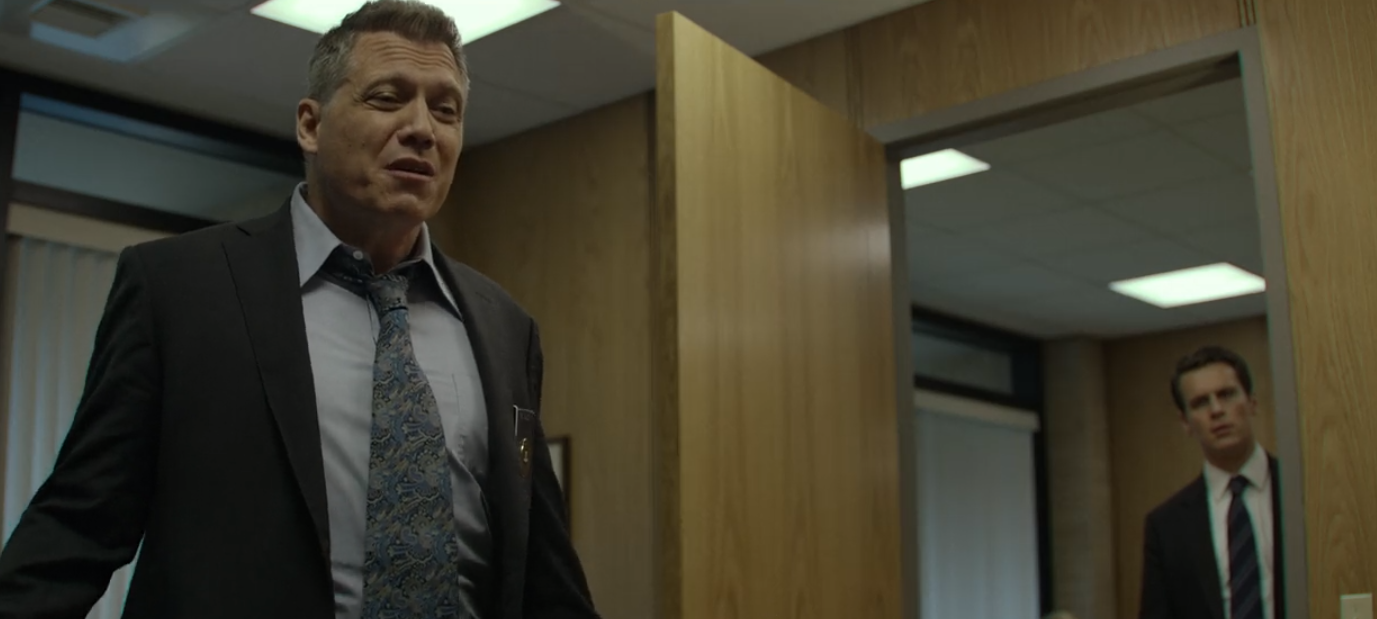 Bill Trench explains his point to his boss in Mindhunter.